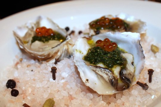 Grilled oysters with chermoula on a bed of rock salt. Paley's Place Bistro & Bar. 2013. Courtesy of Pamela Heiligenthal.
